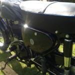 AJS 16MS - 1957 - Side Panel with Badge, Footrest, Shock Absorber, and Chain Guard.