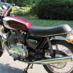 Triumph Trident T160 - 1975 - Exhaust Silencer, Side Panel, Triumph Badge, Shock Absorber and Seat.