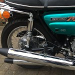 Suzuki GT750J - 1972 - Exhaust System, Swing Arm, Side Panel, Liquid Cooled Badge, Brake Cable and Lever.